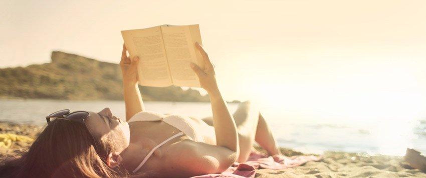 Chica leyendo libro en la playa